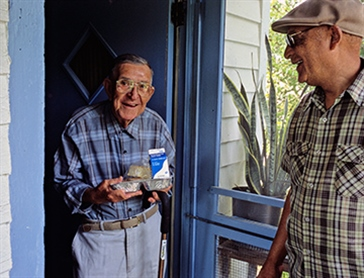 volunteer delivering food to elderly man.jpg